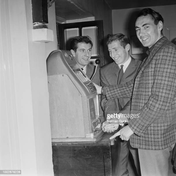 Tottenham Hotspur footballers from left Eddie Clayton Cliff Jones and Alan Gilzean pictured together playing a fruit machine or onearmed bandit...