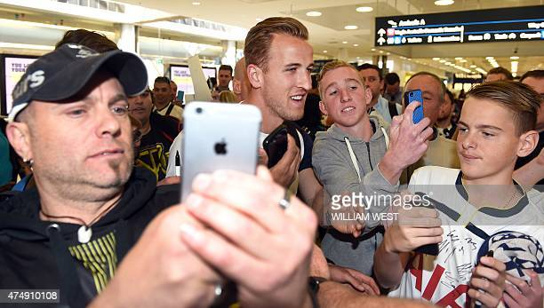Tottenham Hotspur forward Harry Kane is swamped by fans as he is escorted through Sydney Airport on May 28 2015 as the English Premier League team...