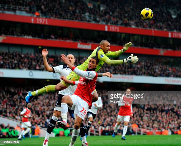 Tottenham Hotspur goalkeeper Heurelho Gomes collides with Marouane Chamakh of Arsenal during the Barclays Premier League match between Arsenal and...