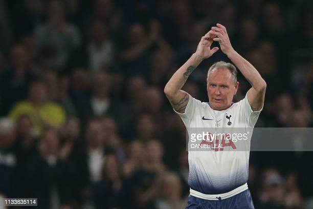 Tottenham Hotspur Legends' English player Paul Gascoigne applauds the crowd as he leaves the pitch during the Legends football match between...