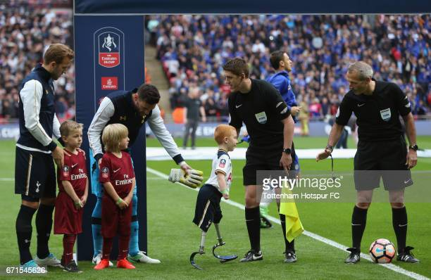Tottenham Hotspur mascot Marshall Janson is greeted by referee Martin Atkinson during The Emirates FA Cup SemiFinal between Chelsea and Tottenham...