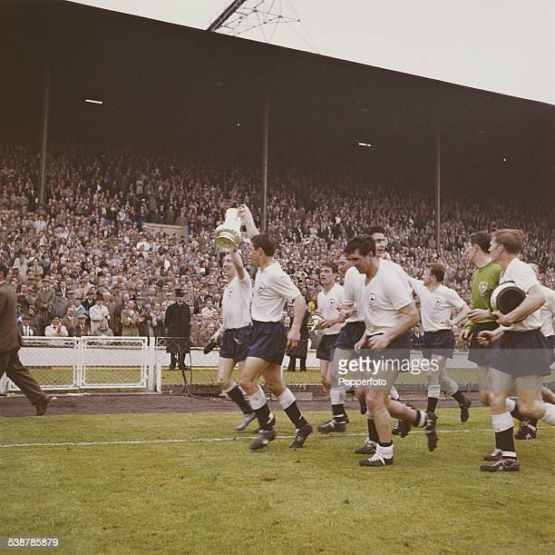 Tottenham Hotspur players hold the Football Association Challenge Cup trophy aloft in front of crowds after Spurs beat Burnley FC 31 at the FA cup...