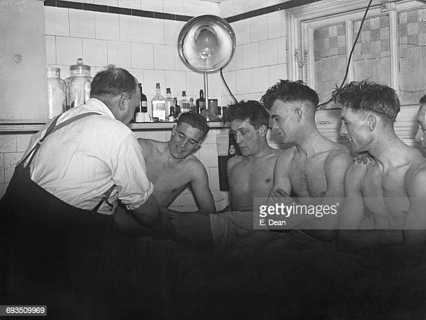 Tottenham Hotspur trainer George Hardy attending to players including team captain Arthur Rowe after a practice game at Spurs' White Hart Lane ground...