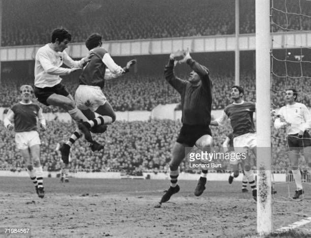 Tottenham Hotspur winger Jimmy Robertson heads the ball goalwards during a match against Arsenal at White Hart Lane 20th January 1968 The ball was...