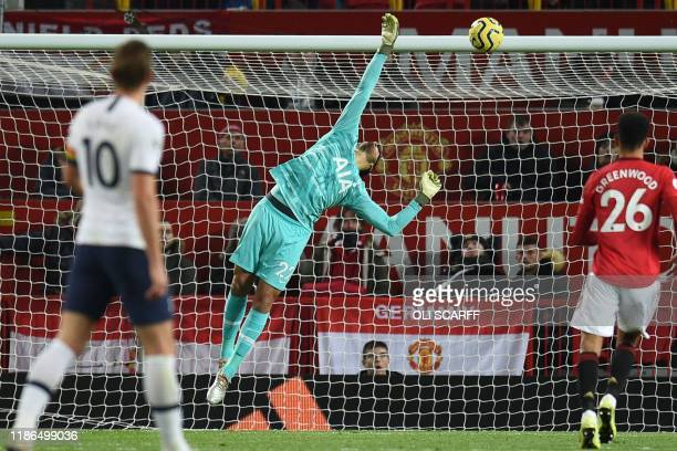 Tottenham Hotspur's Argentinian goalkeeper Paulo Gazzaniga deflects the ball onto the bar from a shot by Manchester United's English striker Marcus...