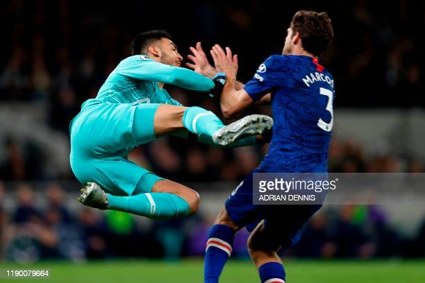 Tottenham Hotspur's Argentinian goalkeeper Paulo Gazzaniga gives away a penalty for this challenge on Chelsea's Spanish defender Marcos Alonso during...