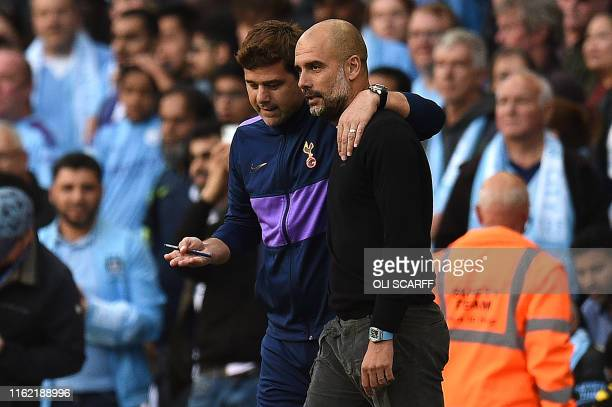 Tottenham Hotspur's Argentinian head coach Mauricio Pochettino and Manchester City's Spanish manager Pep Guardiola talk after the VAR decision ruled...