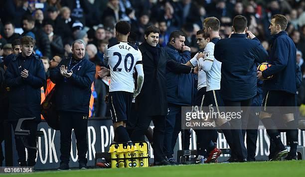 Tottenham Hotspur's Argentinian head coach Mauricio Pochettino congratulates his players including Tottenham Hotspur's English midfielder Dele Alli...