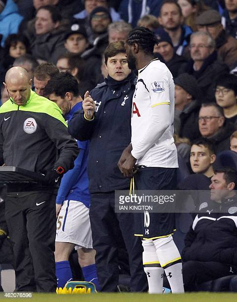 Tottenham Hotspurs Argentinian head coach Mauricio Pochettino talks to Tottenham Hotspur's Togolese striker Emmanuel Adebayor before he comes on as a...