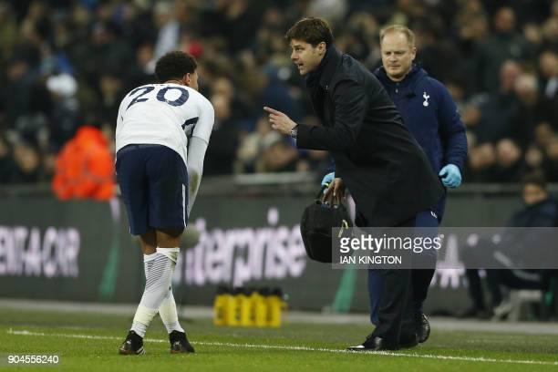 Tottenham Hotspur's Argentinian head coach Mauricio Pochettino talks to Tottenham Hotspur's English midfielder Dele Alli during the English Premier...