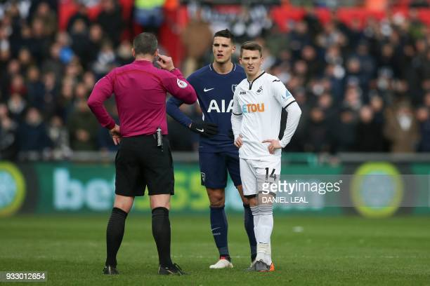 Tottenham Hotspur's Argentinian midfielder Erik Lamela and Swansea City's English midfielder Tom Carroll wait for the decision of the referee during...