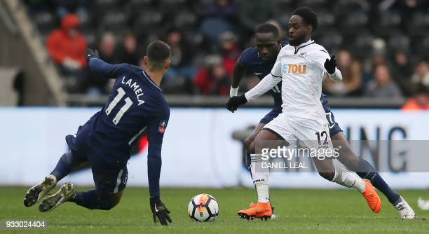 Tottenham Hotspur's Argentinian midfielder Erik Lamela jumps in to challenge Swansea City's English midfielder Nathan Dyer during the English FA Cup...