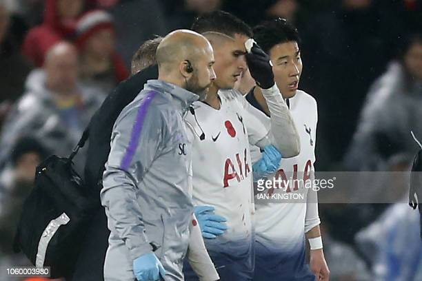 Tottenham Hotspur's Argentinian midfielder Erik Lamela leaves the pitch after picking up a head injury during the English Premier League football...