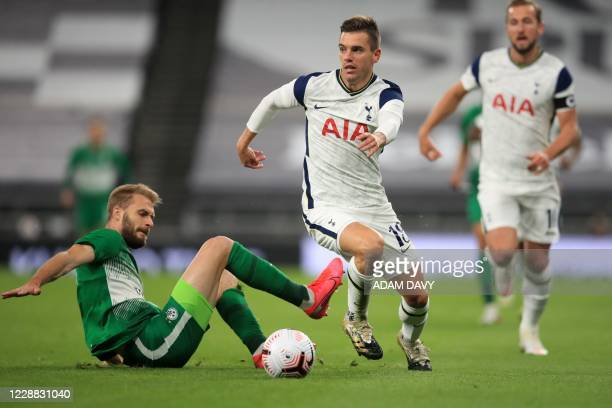 Tottenham Hotspur's Argentinian midfielder Giovani Lo Celso runs past a challenge from Maccabi Haifa's Serbian defender Bogdan Planic during the UEFA...