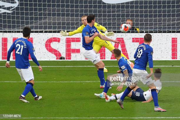 Tottenham Hotspur's Argentinian midfielder Giovani Lo Celso scores the opening goal from a deflection off of Everton's English defender Michael Keane...