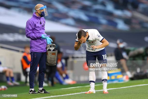 Tottenham Hotspur's Argentinian midfielder Giovani Lo Celso splashes water over his face during the English Premier League football match between...