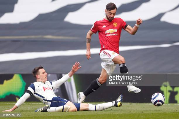 Tottenham Hotspur's Argentinian midfielder Giovani Lo Celso tackles Manchester United's Portuguese midfielder Bruno Fernandes during the English...