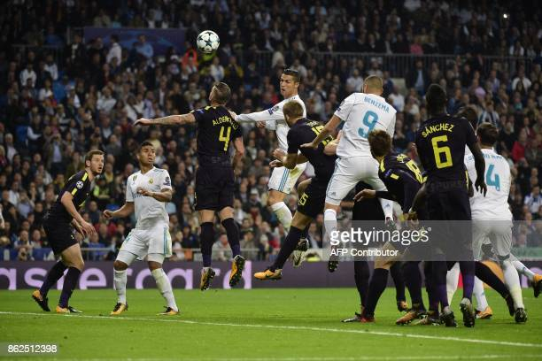 TOPSHOT Tottenham Hotspur's Belgian defender Toby Alderweireld and Real Madrid's Portuguese forward Cristiano Ronaldo jump for the ball during the...