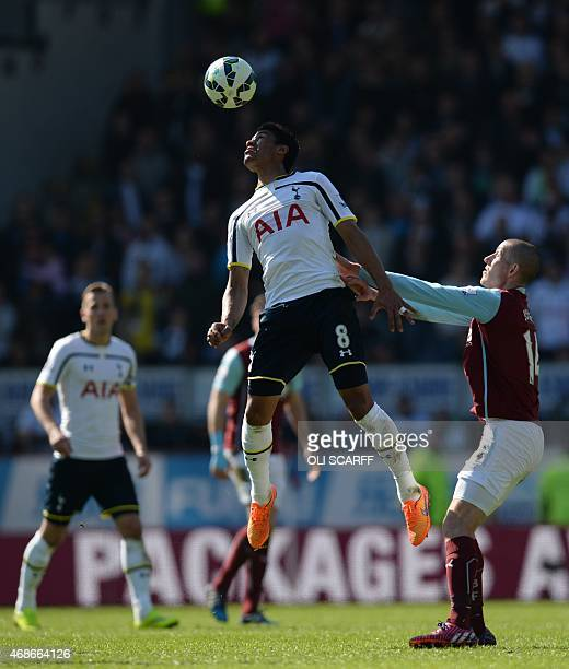 Tottenham Hotspur's Brazilian midfielder Paulinho heads the ball watched by Burnley's English midfielder David Jones during the English Premier...