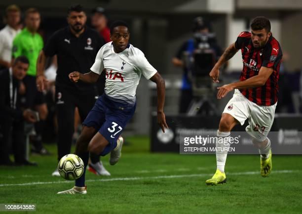 Tottenham Hotspur's British defender Kyle WalkerPeters controls the ball followed by AC Milan's Italian foward Patrick Cutrone during the...