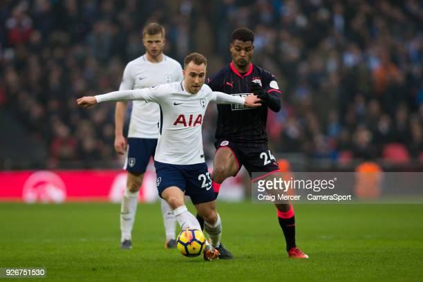 Tottenham Hotspur's Christian Eriksen holds off the challenge from Huddersfield Town's Steve Mounie during the Premier League match between Tottenham...