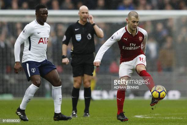 Tottenham Hotspur's Colombian defender Davinson Sanchez looks on as Arsenal's English midfielder Jack Wilshere plays the ball during the English...