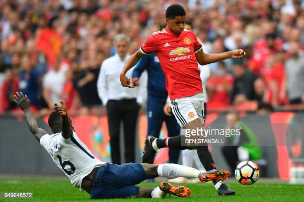 Tottenham Hotspur's Colombian defender Davinson Sanchez tackles Manchester United's English striker Marcus Rashford during the English FA Cup...