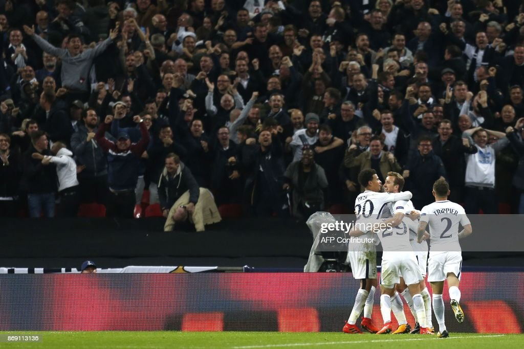 Tottenham Hotspur's Danish midfielder Christian Eriksen celebrates with teammates after scoring their third goal during the UEFA Champions League Group H football match between Tottenham Hotspur and Real Madrid at Wembley Stadium in London, on November 1, 2017. / AFP PHOTO / IKIMAGES / Ian KINGTON