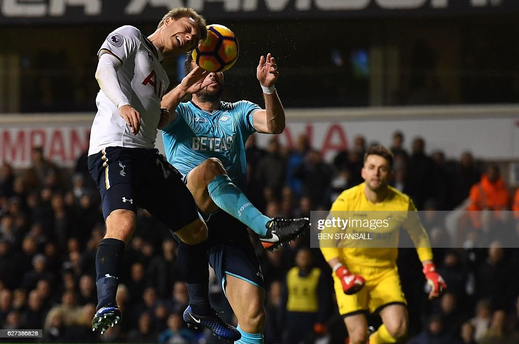 Tottenham Hotspur's Danish midfielder Christian Eriksen (L) heads the ball past Swansea City's Spanish defender Jordi Amat to score his team's fifth goal during the English Premier League football match between Tottenham Hotspur and Swansea City at White Hart Lane in London, on December 3, 2016. Tottenham won the match 5-0. / AFP / Ben STANSALL / RESTRICTED TO EDITORIAL USE. No use with unauthorized audio, video, data, fixture lists, club/league logos or 'live' services. Online in-match use limited to 75 images, no video emulation. No use in betting, games or single club/league/player publications. /