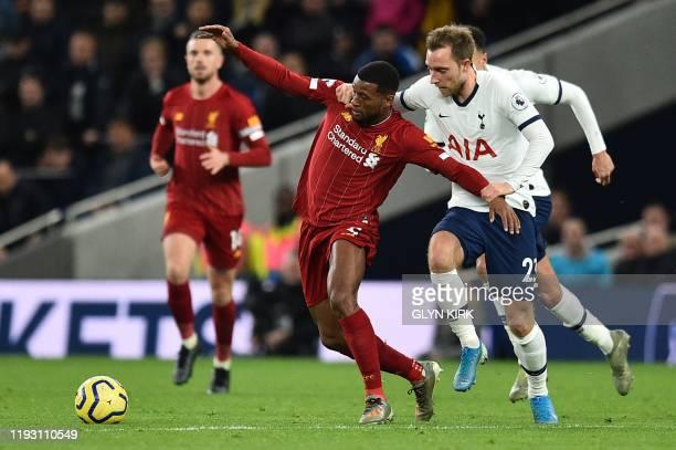 Tottenham Hotspur's Danish midfielder Christian Eriksen holds back Liverpool's Dutch midfielder Georginio Wijnaldum during the English Premier League...