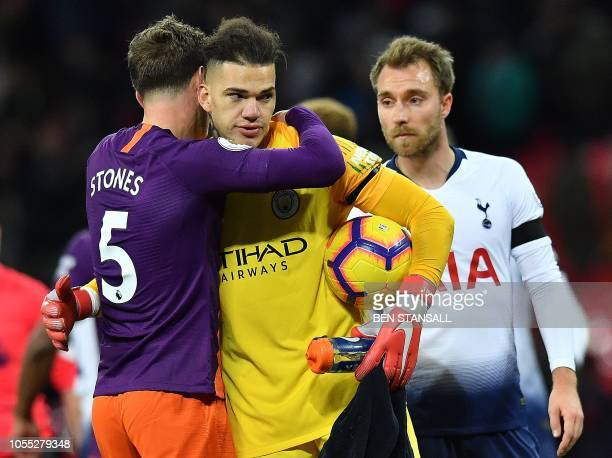 Tottenham Hotspur's Danish midfielder Christian Eriksen reacts as Manchester City's English defender John Stones hugs Manchester City's Brazilian...