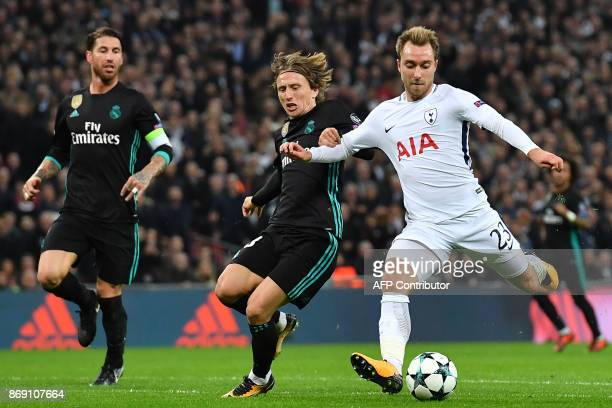 Tottenham Hotspur's Danish midfielder Christian Eriksen shoots past Real Madrid's Croatian midfielder Luka Modric to score their third goal during...