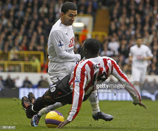 Tottenham Hotspur's English Aaron Lennon skips over a tackle from Sunderland's Trinidadian midfielder Dwight Yorke during the Premiership football...
