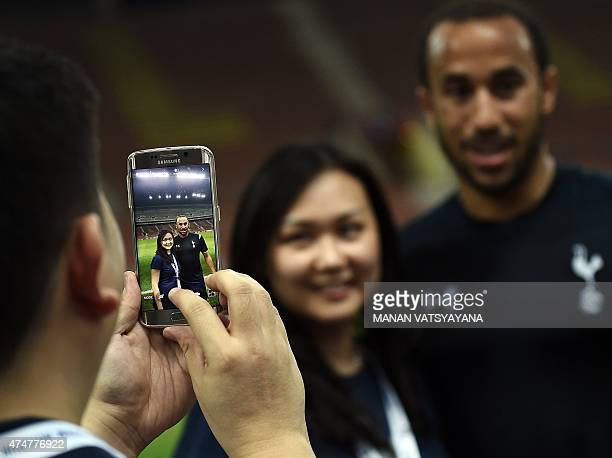 Tottenham Hotspur's English midfielder Andros Townsend poses for a photograph with a fan after a practice session at the Shah Alam Stadium on May 26...