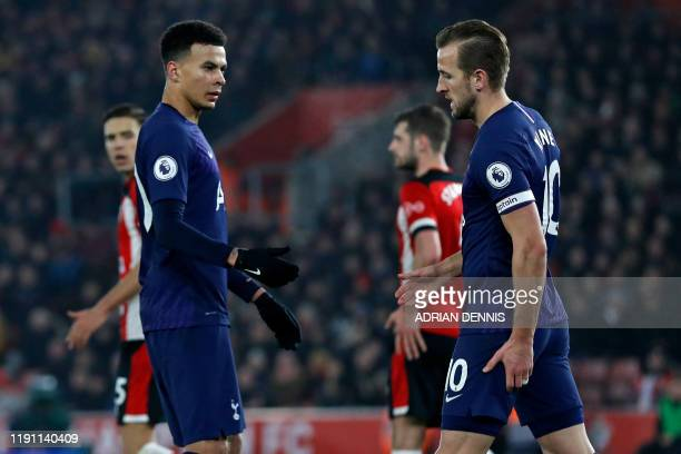 Tottenham Hotspur's English midfielder Dele Alli checks on Tottenham Hotspur's English striker Harry Kane after he appears to have picked up an...