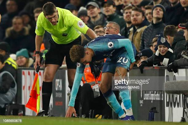 Tottenham Hotspur's English midfielder Dele Alli holds his leg after appearing to pick up an injury during the English Premier League football match...