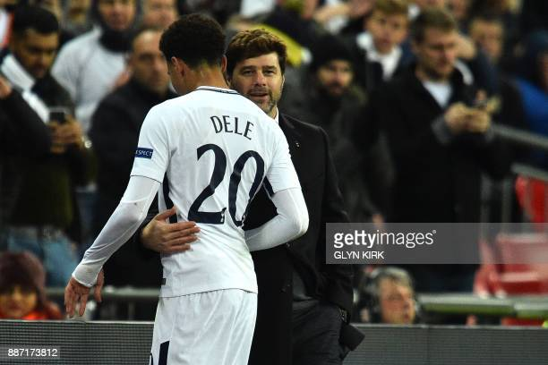 Tottenham Hotspur's English midfielder Dele Alli is embraced by Tottenham Hotspur's Argentinian head coach Mauricio Pochettino as he leaves the pitch...