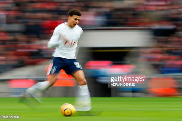 Tottenham Hotspur's English midfielder Dele Alli passes the ball on his way to Harry Kane scoring his third goal their fifth during the English...
