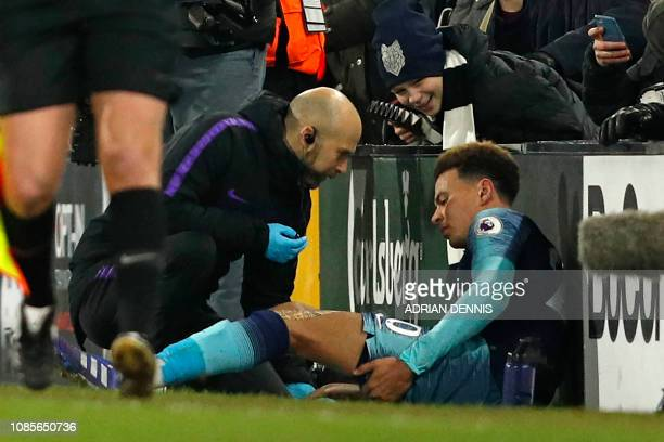 Tottenham Hotspur's English midfielder Dele Alli receives medical attention as he holds his leg after appearing to pick up an injury during the...