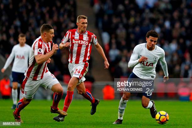 Tottenham Hotspur's English midfielder Dele Alli runs away from Stoke City's Austrian defender Kevin Wimmer and Stoke City's Scottish midfielder...