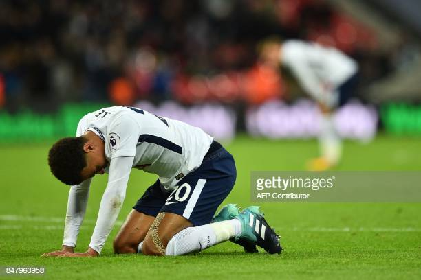 Tottenham Hotspur's English midfielder Dele Alli sinks to his knees at the final whistle in the English Premier League football match between...