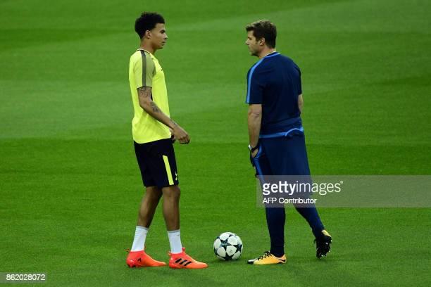 Tottenham Hotspur's English midfielder Dele Alli speaks to Tottenham Hotspur's Argentinian coach Mauricio Pochettino during a training session in...