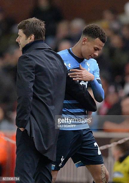 Tottenham Hotspur's English midfielder Dele Alli speaks with Tottenham Hotspur's Argentinian head coach Mauricio Pochettino as he is substituted...