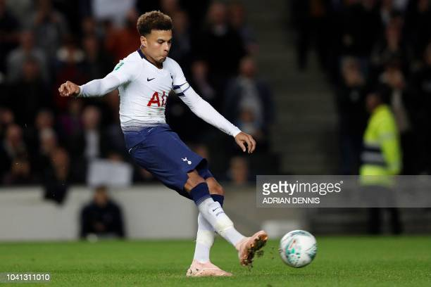 Tottenham Hotspur's English midfielder Dele Alli strikes the ball to score the winning penalty during the English League Cup third round football...