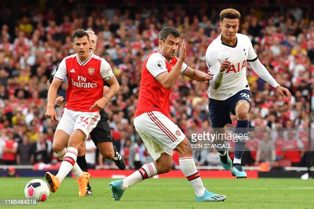 Tottenham Hotspur's English midfielder Dele Alli vies with Arsenal's Greek defender Sokratis Papastathopoulos during the English Premier League...