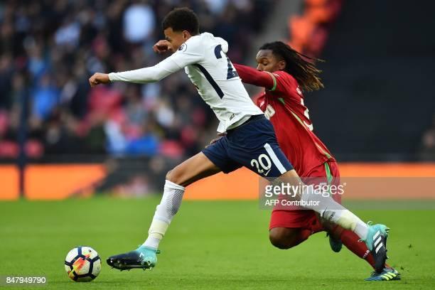 Tottenham Hotspur's English midfielder Dele Alli vies with Swansea City's Portuguese midfielder Renato Sanches during the English Premier League...
