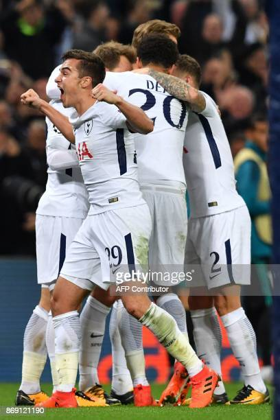 Tottenham Hotspur's English midfielder Harry Winks and teammates celebrate Tottenham Hotspur's Danish midfielder Christian Eriksen's goal during the...