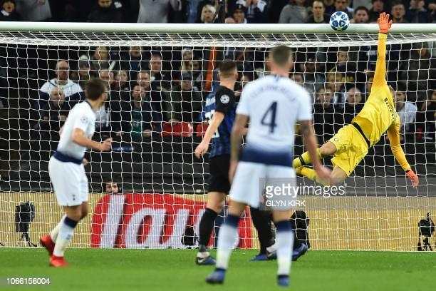 Tottenham Hotspur's English midfielder Harry Winks sees his shot hit the bar as Inter Milan's Slovenian goalkeeper Samir Handanovic dives in vain...