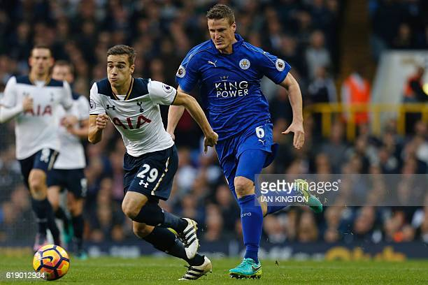 Tottenham Hotspur's English midfielder Harry Winks vies with Leicester City's German defender Robert Huth during the English Premier League football...