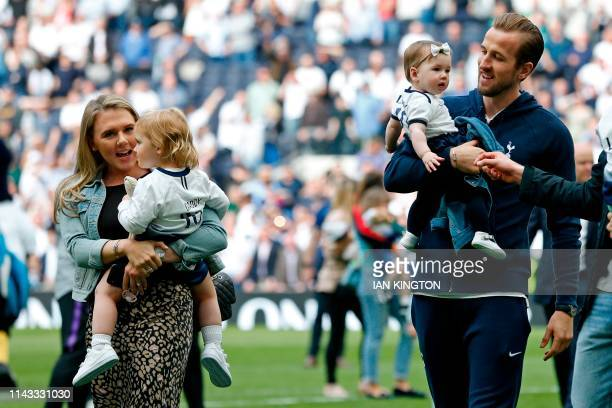 Tottenham Hotspur's English striker Harry Kane and his partner Katie Goodland walk on th epitch with their two daughters after the English Premier...